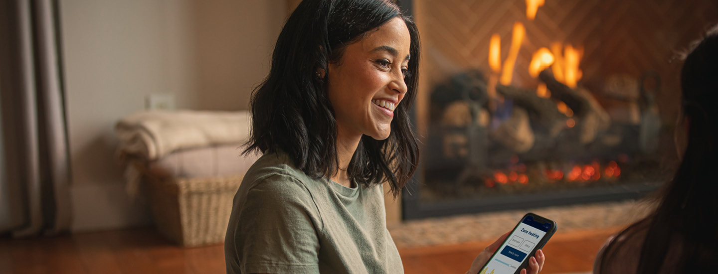 A woman sitting in her living room by a fireplace, smiling and holding a smartphone. The smartphone features a home heating app. (20-064.18)