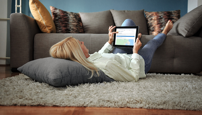 Woman laying down looking at tablet