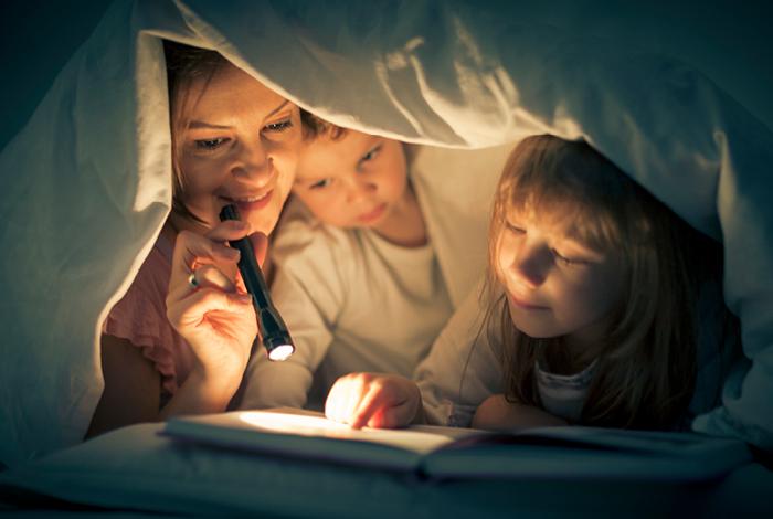 Family huddling under a blanket reading