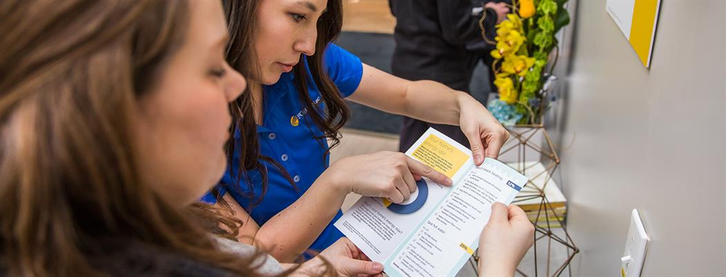 FortisBC street team ambassador showing an energy conservation brochure to someone at an event (18-150.11)
