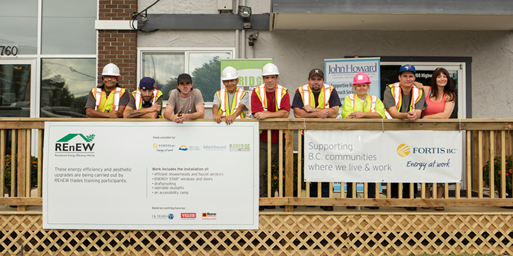 A group of recent grads of the REnEW program standing on the front deck of an apartment building  (18-150.11)