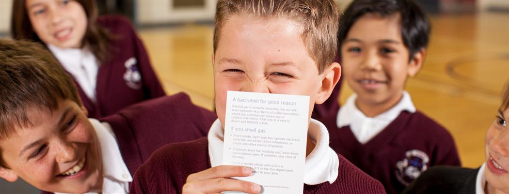 A elementary school boy smelling a natural gas scratch 'n sniff card. (18-150.13)